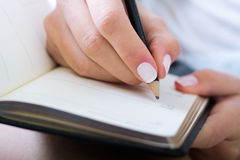 Woman taking notes at home. Young woman taking notes at home Royalty Free Stock Photo