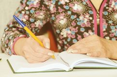 Woman taking notes in Notepad. She works as a dispatcher at home Royalty Free Stock Photos