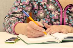 Woman taking notes in Notepad. She works as a dispatcher at home Stock Photography