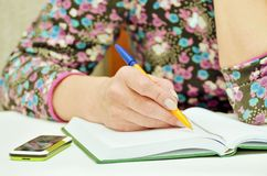 Woman taking notes in Notepad. She works as a dispatcher at home Stock Photo