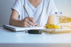 Woman taking notes and planning,Saving money for cars with coins on mini shopping trolley cart,Car finance and loan concept. Woman taking notes and planning Stock Photography