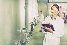 Woman taking notes on wine factory Stock Images