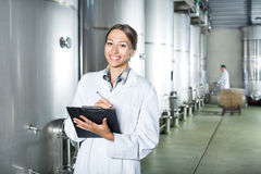 Woman taking notes on wine factory Stock Photo