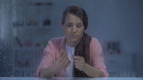 Woman taking off engagement ring behind rainy window, upset after break up. Stock footage stock footage