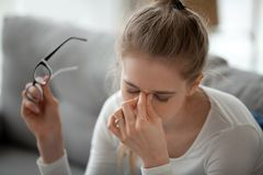 Free Woman Taking Off Eyeglasses Massaging Nose Bridge Stock Photos - 130410083