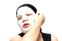 Woman taking off facial mask on face Stock Photos