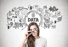 Woman taking off glasses, big data. Serious woman wearing a white sweater and taking off her glasses standing near a concrete wall with a big data sketch drawn stock image