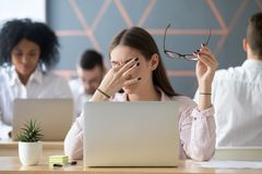 Woman taking off glasses tired of work, eyes fatigue concept. Young women taking off glasses tired of computer work, exhausted student or employee suffering from stock photos