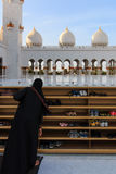 Woman taking off her shoes before entering the Sheikh Zayed Grand Mosque Royalty Free Stock Photography