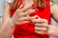 Woman is taking off her wedding ring - divorce concept. Disappointed woman is taking off her wedding ring - divorce concept Royalty Free Stock Photos