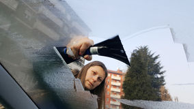 WoMan taking off ice from the windscreen Royalty Free Stock Image