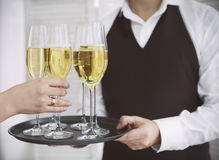 Woman taking one glass of champagne from the tray Royalty Free Stock Photos