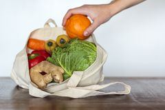 Woman taking a orange from eco bag with groceries stock image