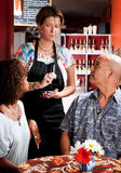 Woman taking order from couple in coffee house Royalty Free Stock Photos