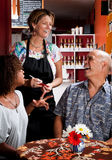 Woman taking order from couple in coffee house Royalty Free Stock Images