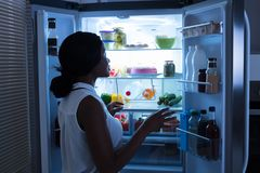 Woman Taking Out Bottle From Refrigerator stock photos