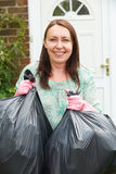 Woman Taking Out Garbage In Bags Royalty Free Stock Photo