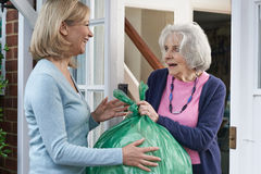 Woman Taking Out Trash For Elderly Neighbour Royalty Free Stock Images