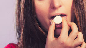 Woman taking painkiller pill tablet. Health care. Stock Photography