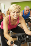Woman Taking Part In Spinning Class In Gym Stock Photo