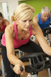 Woman Taking Part In Spinning Class In Gym Royalty Free Stock Images