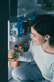 Woman taking a pastry out of the fridge. Woman having an unhealthy snack, she is taking a delicious pastry out of the fridge royalty free stock images