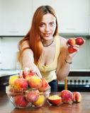 Woman taking peaches at table in home Stock Images