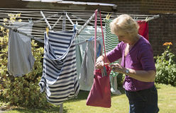 Woman taking pegs from a peg bag to hang washing Stock Photo