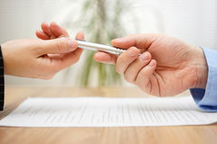 Woman is taking pen from businessman to sign the document Royalty Free Stock Images