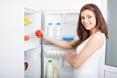 Woman taking pepper from fridge. Woman taking red sweet pepper from her fridge, looking at camera stock photo