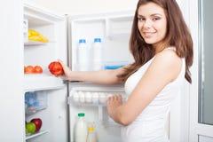 Woman taking pepper from fridge Stock Image