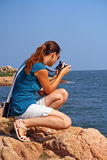 Woman taking a photo. Young woman on the coast is taking a photo with the digital camera stock photo