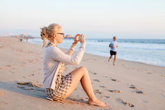 Woman taking photo on beach Royalty Free Stock Image