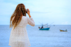 Woman taking photo on beach Stock Images