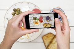 Woman taking a photo of breakfast table. stock photo