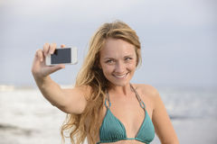 Woman taking photo with cellphone on the beach Stock Photography