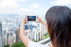 Woman taking photo with cellphone in Hong Kong Royalty Free Stock Photography