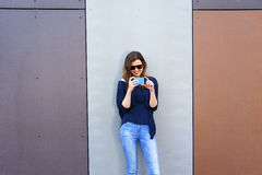 Woman taking photo with cellphone by the wall. Happy girl in cit Stock Photos