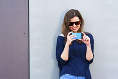 Woman taking photo with cellphone by the wall. Happy girl in cit Stock Photo