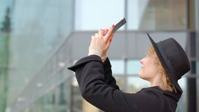 Woman taking photo of cityscape view with cellphone. walking in the center of a big city stock video footage