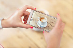 Woman taking photo of coffee with smartphone Stock Image