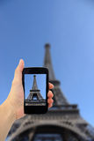 Woman taking photo of Eiffel Tower with cell phone Royalty Free Stock Image