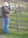A woman taking a photo in a field. A woman resting on a wooden gate in a field while taking a photo Royalty Free Stock Images
