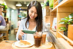 Woman taking photo on food in cafe Royalty Free Stock Photo