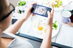 Woman Taking Photo of Food in Cafe. High angle closeup of unrecognizable young woman taking photo of beautiful food via smartphone while enjoying lunch in cafe stock photos