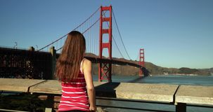 Woman taking photo of the Golden Gate Bridge with smartphone. Rear view of a young Caucasian woman with long dark hair using her smartphone to take a photo of stock video