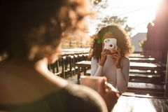 Woman clicking photo at a coffee shop Stock Photo