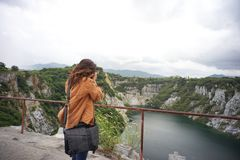 woman taking a photo with her phone of amazing mountains landscape stock photography