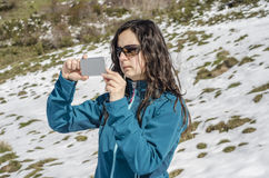 Woman taking photo with her smartphone in winter mountains. In Montaña Palentina, Spain Royalty Free Stock Images