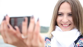 Woman taking photo of herself with cell on sea shore Stock Photos